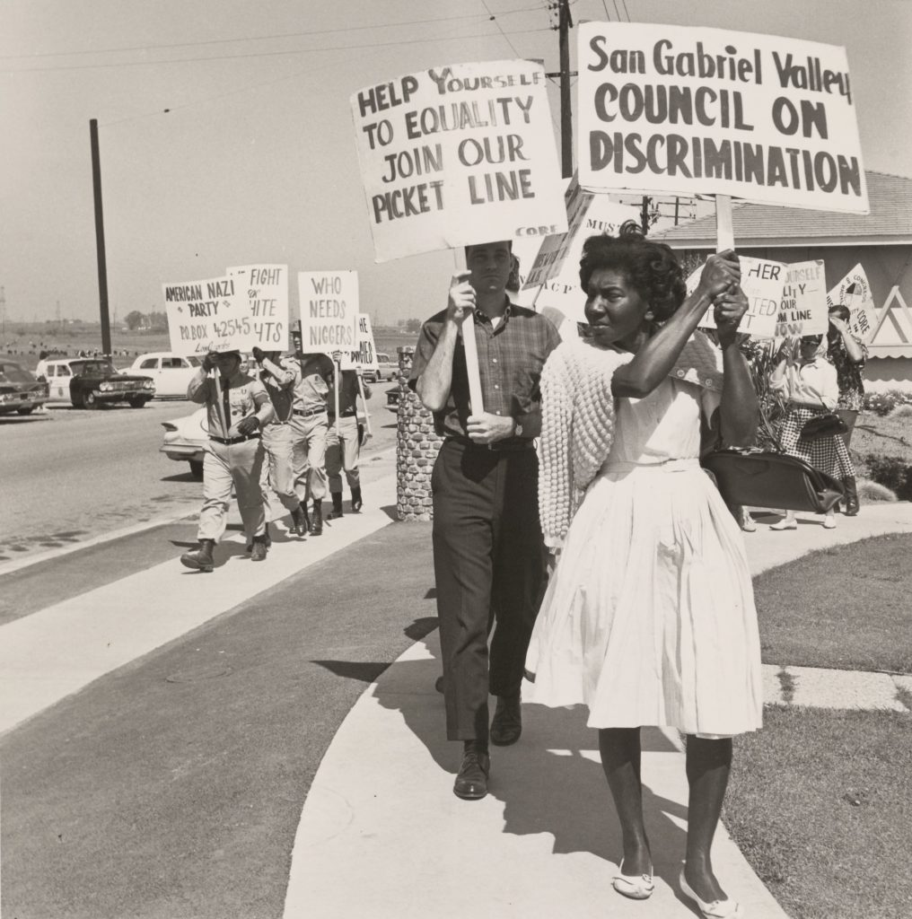1.Fig_6. CHARLES BRITTIN, NEAR LOS ANGELES, CA, 1963. Los Angeles, Getty Research Institute. Activists picketing at a demonstration for housing equality while uniformed American Nazi Party members counterprotest in the background with signs displaying anti-integration slogans and racist epithets.