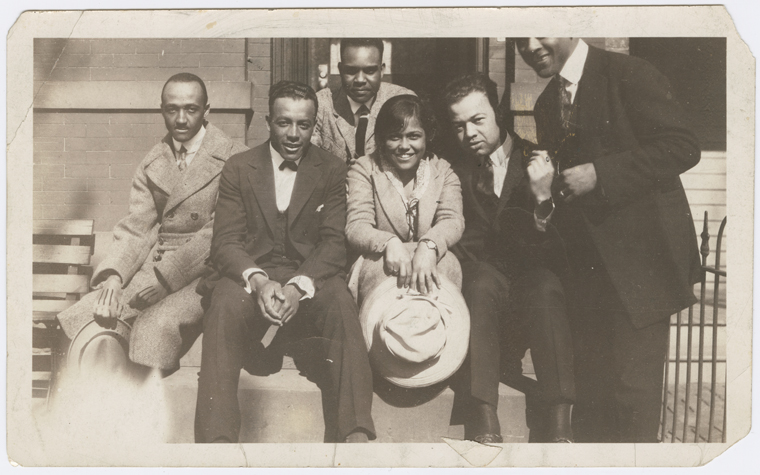 "Harlem Renaissance writer Gwendolyn Bennett (center) with a group of male friends (left to right): Charley Boyd, Hoggie Payne, Jayfus Ward, ""The Fat One"" Hoffman and ""Bon Bon"" Simmons, circa 1920s."" (Schomburg Center for Research in Black Culture, Photographs and Prints Division, The New York Public Library)"