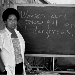 "Audre Lorde standing in front of board reading ""Women are powerful and dangerous."" Source: The Guardian."