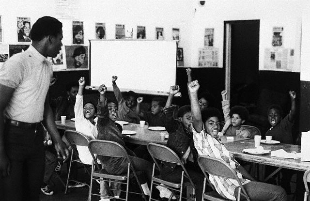 20 Dec 1969, San Francisco, California, USA --- A teacher leads his students with the black power salute and slogans at a Black Panther liberation school. --- Image by © Bettmann/CORBIS