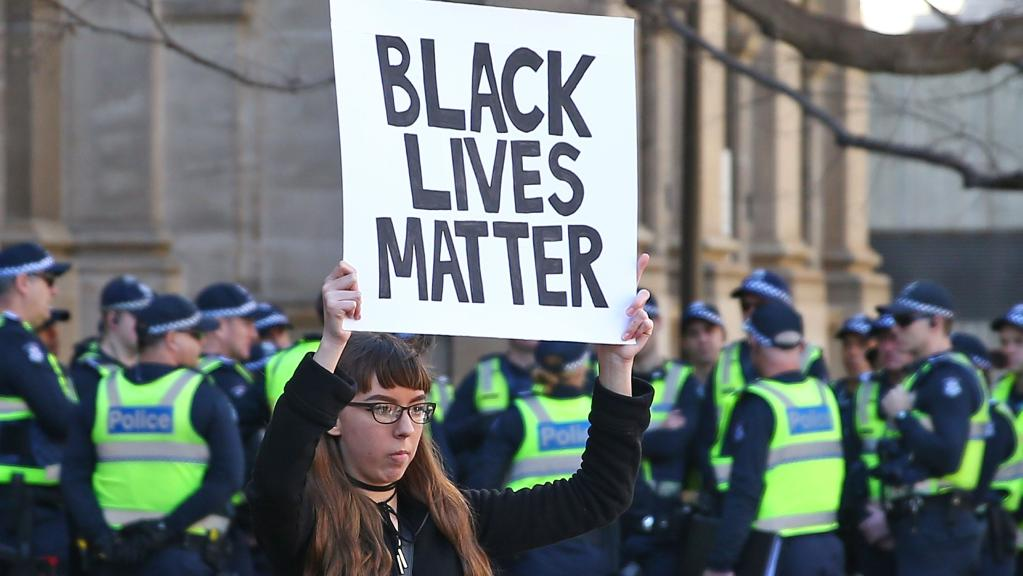 A woman holds a Black Lives Matter poster during a rally to support the Black Lives Matter movement. Picture: Scott Barbour/Getty Images