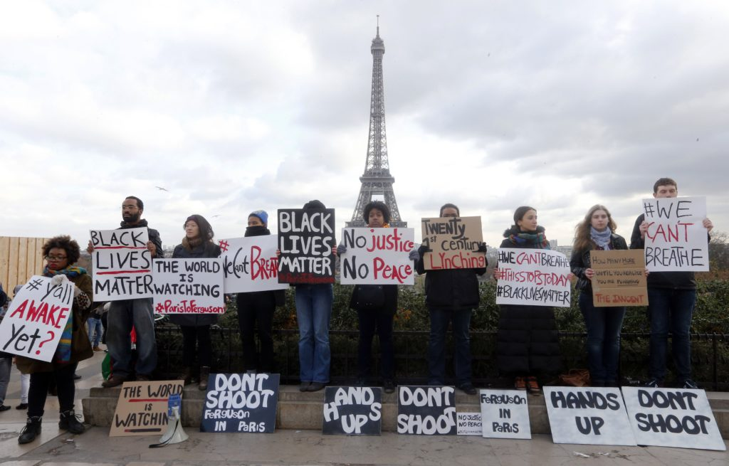 Protesters hold placards on December 6, 2014 on the Trocadero esplanade in Paris during a demonstration against police violence in France and in the US. The Paris demonstration took place after thousands of demonstrators marched in major cities across the United States in a fresh wave of protests against a spate of killings of unarmed black men by white police officers. AFP PHOTO/FRANCOIS GUILLOT (Photo credit should read FRANCOIS GUILLOT/AFP/Getty Images)