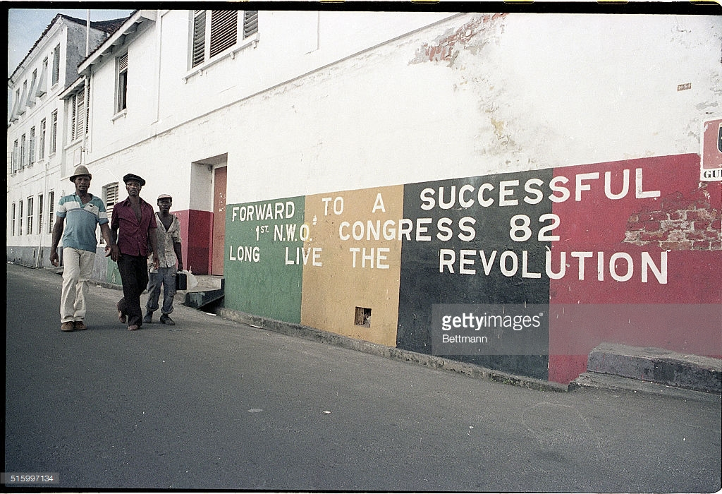 (Original Caption) 10/1983-Grenada: Residents of Grenada walk past a mural that reads: 'Forward to Successful NWO Congress 82, Long Live the Revolution.' Photographed during the U.S. invasion of Grenada.