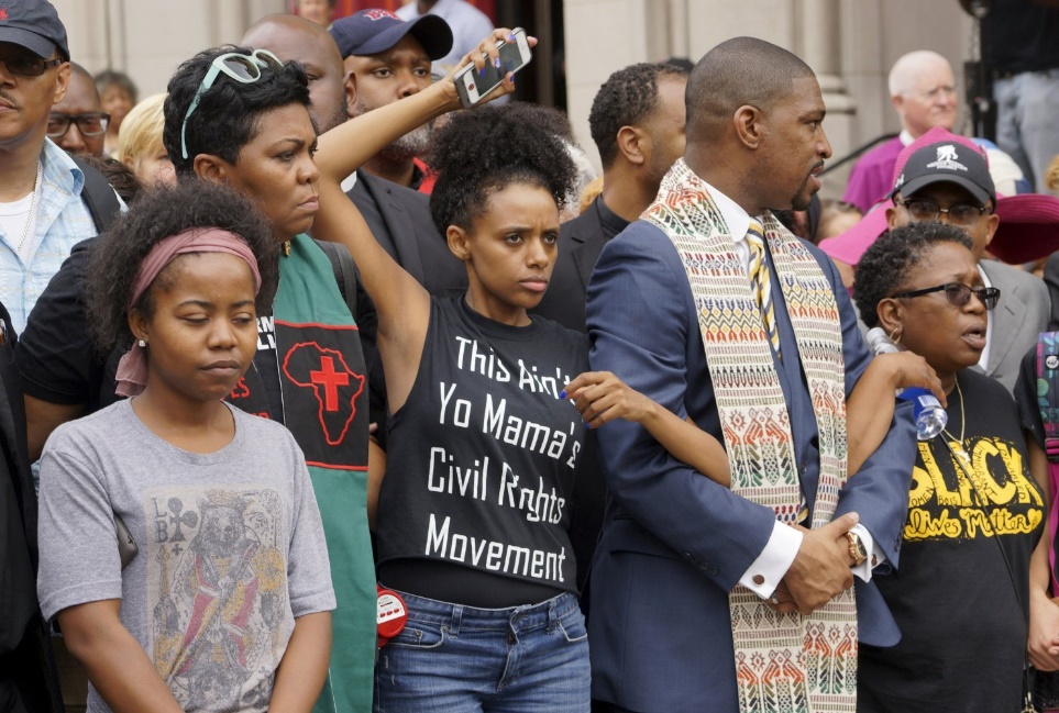 Protesters prepare to march in downtown St. Louis August 10, 2015. Rahiel Tesfamariam, in the black graphic t-shirt, is linking arms with the Rev. Starsky Wilson. (Washington Post, Rick Wilking/Reuters)