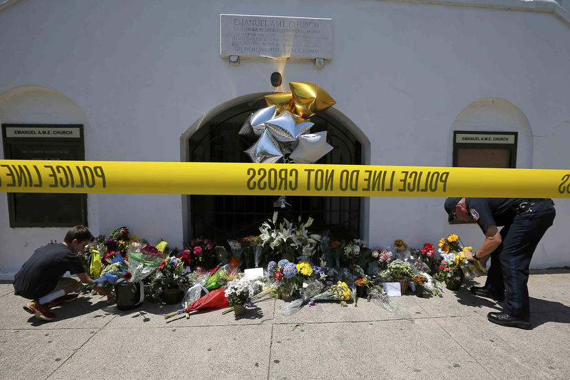 Nine-year-old Liam Eller (L), helps a police officer move flowers left behind outside Emanuel African Methodist Episcopal Church after the street was re-opened a day after a mass shooting left nine dead during a bible study at the church in Charleston, South Carolina June 18, 2015. A 21-year-old white gunman accused of killing nine people at a historic church was arrested on Thursday, said U.S. officials, who are investigating the attack as a hate crime. REUTERS/Brian Snyder
