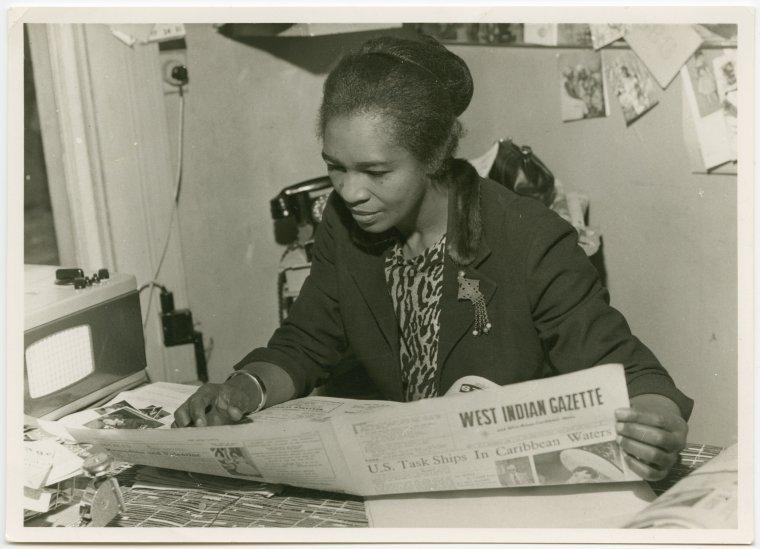 Claudia Jones reading The West Indian Gazette in London in the 1960s (Credit: Schomburg