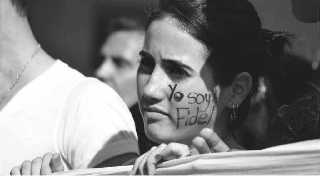 """Woman wearing face paint, """"Yo soy Fidel"""" (I am Fidel). Source: www.granma.cu."""