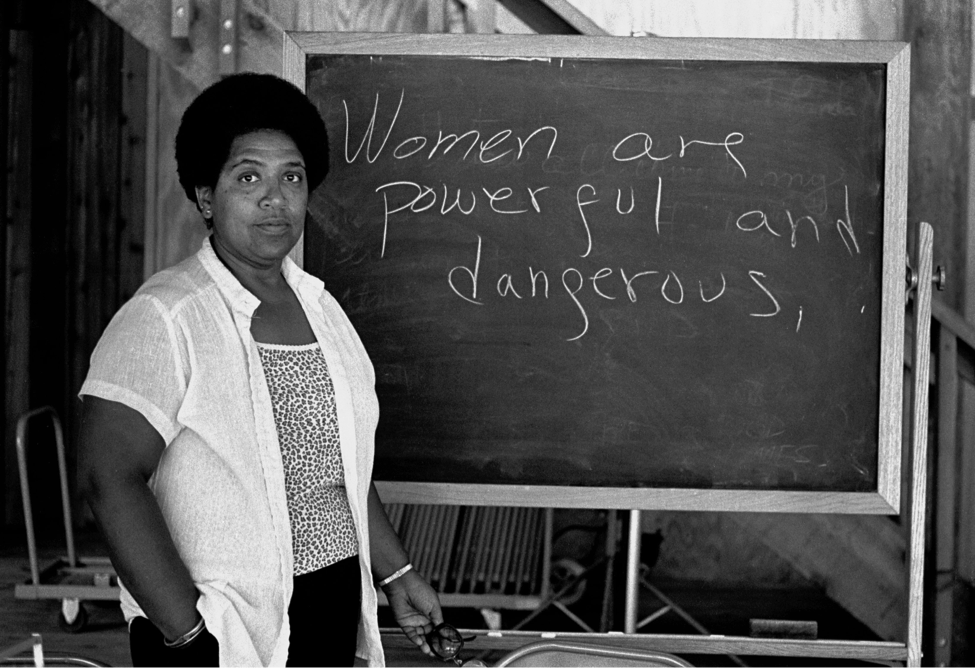 """Audre Lorde standing in front of board reading """"Women are powerful and dangerous."""" Source: The Guardian."""