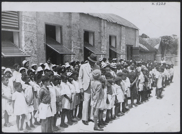 'Poor children of Bridgetown, Barbados, receive free lunch provided daily by the Childrens' Goodwill League, under the chairmanship of John Beckles, who is chatting with the children'. Photo: Flickr/Official Barbados photograph compiled by Central Office of Information.