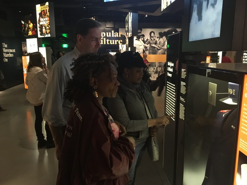 Students Viewing a NOI Fruit of Islam Uniform in the Religion and Black Power Section. Photo: Author.