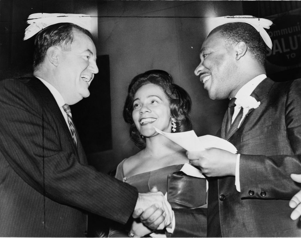 Then Vice President-elect Hubert H. Humphrey (left), alongside Coretta Scott King (center), and Civil Rights Leader and Nobel Peace Prize Laureate Dr. Martin Luther King, Jr. (right), at a rally at Harlem's 369th Regiment Armory on December 17, 1964. Photo: Library of Congress.