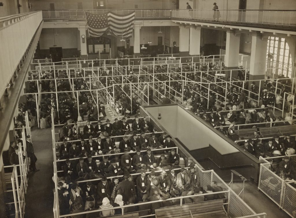 """The pens at Ellis Island, Registry Room (or Great Hall). These people have passed the first mental inspection,"" Edwin Levick, ca. 1902-1913. Photo: New York Public Library Digital Collections."