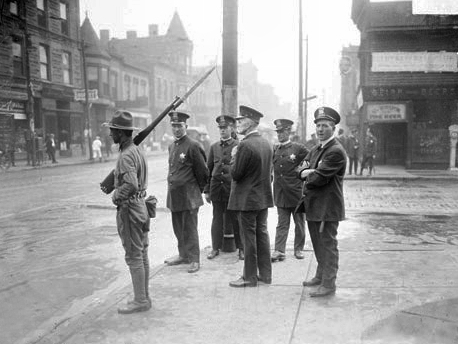 Five policemen and one soldier with a rifle standing on a street corner during the race riots in the Douglas community area of Chicago, 1919. Photo: Chicago Daily News/Wikimedia.